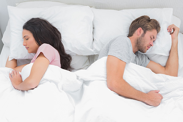 Couple sleeping back to back in their bed